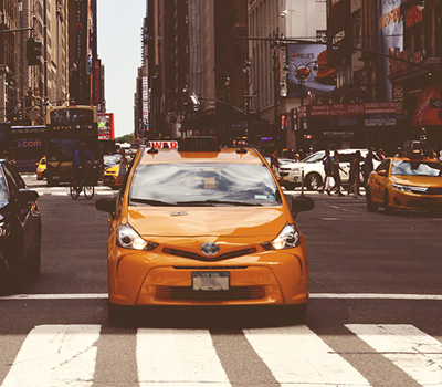 Yellow Uber Taxi Standing in Red Light in New York City