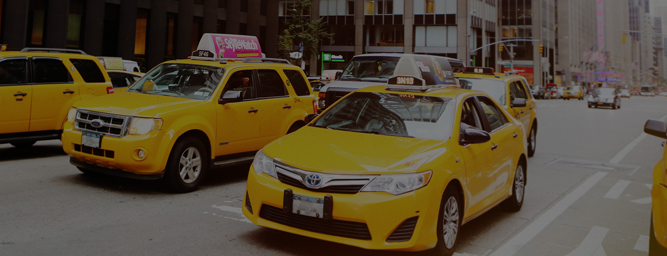 Many Yellow Rideshare Taxis in New York City Street
